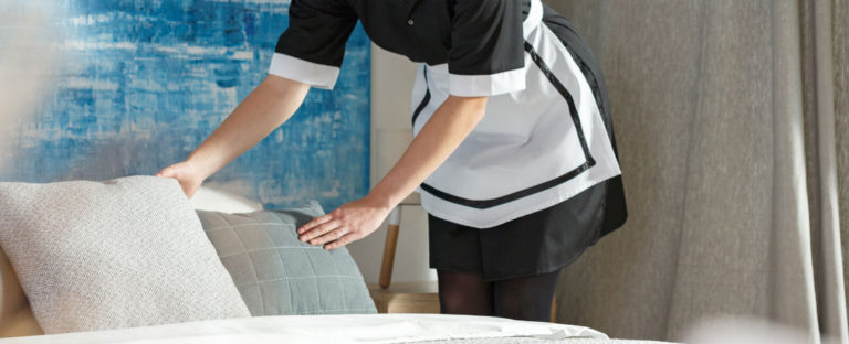 A housekeeper fluffing up the pillows